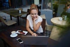 Jeune indépendant féminin réussi à l'aide de l'ordinateur portable pour le travail à distance tout en se reposant dans la barre d Photo stock
