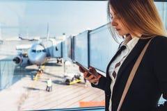 Jeune indépendant féminin réussi tenant la fenêtre proche à l'aéroport stockant un service de mini-messages de téléphone Photo libre de droits