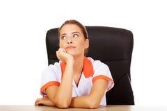 Jeune infirmière féminine fatiguée de doctoror s'asseyant derrière le bureau Image libre de droits