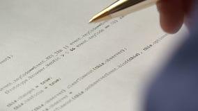 Jeune informaticien vérifiant le code sur le papier banque de vidéos