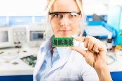 Jeune ingénieur électronicien féminin jugeant le module de mémoire disponible photographie stock