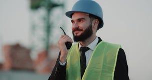 Jeune ingénieur au chantier de construction portant un casque de sécurité et parlant avec ses travailleurs employant une radio banque de vidéos