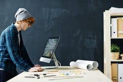 Jeune ingénieur contemporain sur le lieu de travail Photographie stock