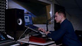 jeune ingénieur du son 4K dans le studio d'enregistrement utilisant l'ordinateur portable au bureau de mélange banque de vidéos