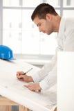 Jeune ingénieur effectuant des plans Images stock
