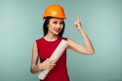 Jeune ingénieur féminin dans le casque orange avec le doigt de points de dessins d'isolement sur le fond bleu photographie stock