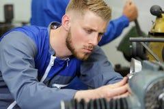 Jeune ingénieur utilisant des machines dans l'atelier image libre de droits
