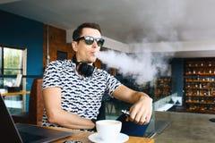 Jeune insunglasse bel d'homme de hippie se reposant en café avec une tasse de café, de vaping et de libérations un nuage de vapeu Photo stock
