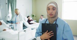 Jeune interne féminin faisant des notes dans une salle d'hôpital 4k clips vidéos