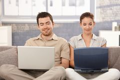 Jeune Internet de furetage de couples à la maison souriant Images stock