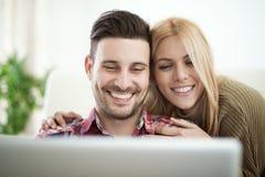 Jeune Internet de lecture rapide de couples à la maison, utilisant l'ordinateur portable et le sourire Photo stock