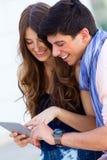 Jeune Internet heureux de lecture rapide de couples avec le comprimé numérique dans Images stock