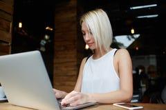 Jeune introduction au clavier de fille de hippie sur son ordinateur portable portatif tout en se reposant dans le café moderne, Photographie stock libre de droits