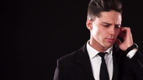Jeune James Bond dans un costume écoute le fait qui dans son écouteur spécial banque de vidéos