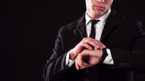 Jeune James Bond vérifie sa montre-bracelet banque de vidéos