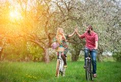 Jeune jardin affectueux de bicyclettes d'équitation de couples au printemps Images libres de droits