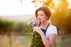 Jeune jardinier en ses fleurs sentantes de jardin, nature ensoleillée photographie stock libre de droits