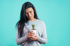 Jeune jardinier féminin avec le pot de fleur photos stock