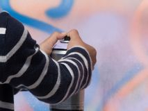 Jeune jet de peinture de main d'artiste d'art mural photos stock