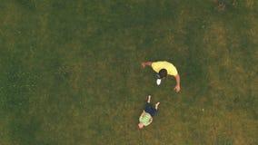 Jeune jeu de garçon avec le père sur la pelouse, tir aérien banque de vidéos