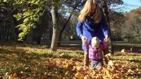 Jeune jeu de mère avec le petit bébé dans le jardin d'automne 4K clips vidéos
