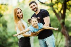 Jeune jeu heureux de famille en parc d'été La mère, le père et la fille volent en parc d'été Images libres de droits
