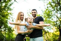 Jeune jeu heureux de famille en parc d'été La mère, le père et la fille volent en parc d'été Photos libres de droits
