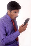 Jeune jeune homme d'affaires shoutting pour téléphoner sur un fond blanc Photos stock