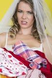 Jeune jeune mariée attirante jugeant la blanchisserie sale fâchée et bouleversée photographie stock