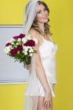 Jeune jeune mariée attirante tenant des fleurs de bouquet de mariage Photographie stock