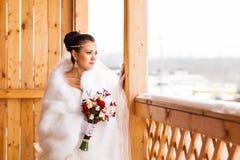 Jeune jeune mariée avec le bouquet de fleur dans l'horaire d'hiver photographie stock