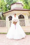 Jeune jeune mariée dans la robe de mariage tenant le bouquet images stock