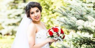 Jeune jeune mariée dans la robe de mariage tenant le bouquet image stock