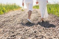 Jeune jeune mariée et fiancé heureux de couples marchant en parc Photographie stock