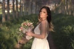 Jeune jeune mariée magnifique avec la peau parfaite et les yeux verts tenant un bouquet nuptiale Photo libre de droits