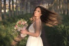 Jeune jeune mariée magnifique avec la peau parfaite et les yeux verts tenant un bouquet nuptiale Photographie stock