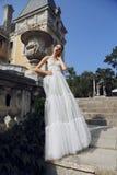 Jeune jeune mariée magnifique avec les cheveux foncés dans la robe de mariage élégante photo stock