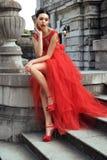 Jeune jeune mariée magnifique avec les cheveux foncés dans la robe de mariage rouge élégante photo stock