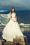 Jeune jeune mariée magnifique dans la robe de mariage luxueuse se tenant sur la falaise Photo stock