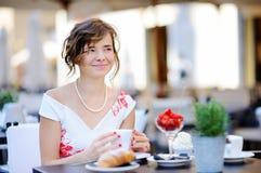 Jeune jeune mariée prenant le petit déjeuner et buvant du café à l'extérieur Photo libre de droits