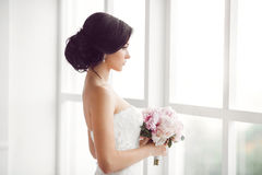 Jeune jeune mariée renversante tenant le bouquet Photo stock