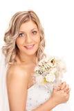 Jeune jeune mariée tenant une fleur de mariage Images stock