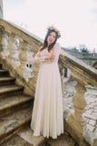 Jeune jeune mariée avec du charme en longue robe de mariage blanche et guirlande florale reculant sur les vieux escaliers en pier Image libre de droits