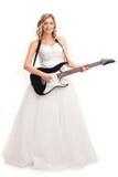 Jeune jeune mariée joyeuse jouant la guitare électrique Photographie stock