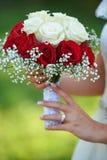 Jeune jeune mariée le jour du mariage tenant le bouquet Photos stock