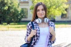 Jeune joli étudiant de sourire avec le standi de sac à dos et d'écouteurs photo libre de droits
