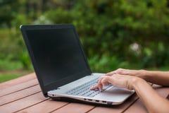 Jeune joli étudiant de sourire causant avec des amis sur l'ordinateur portable en parc d'été Image libre de droits
