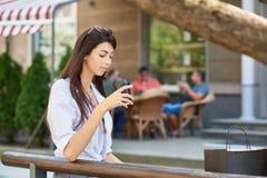 Jeune joli étudiant regardant sur la tasse de papier avec du café, se reposant sur le banc en bois photographie stock libre de droits