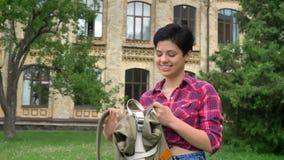 Jeune joli étudiant universitaire avec le sac à dos de port noir et le sourire de cheveux courts, se tenant en parc près de l'uni banque de vidéos