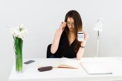Jeune joli café potable de femme d'affaires sur son lieu de travail image libre de droits